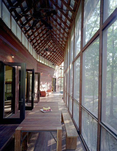 Several sets of aluminum-and-glass French doors open from the bunkroom onto the screen porch. Panton and his team made the dining table and benches on-site; the tongue-and-groove benches and table legs are locally milled cedar, and the top is Brazilian Tigerwood. Photo 9 of Texas Bunkhouse modern home