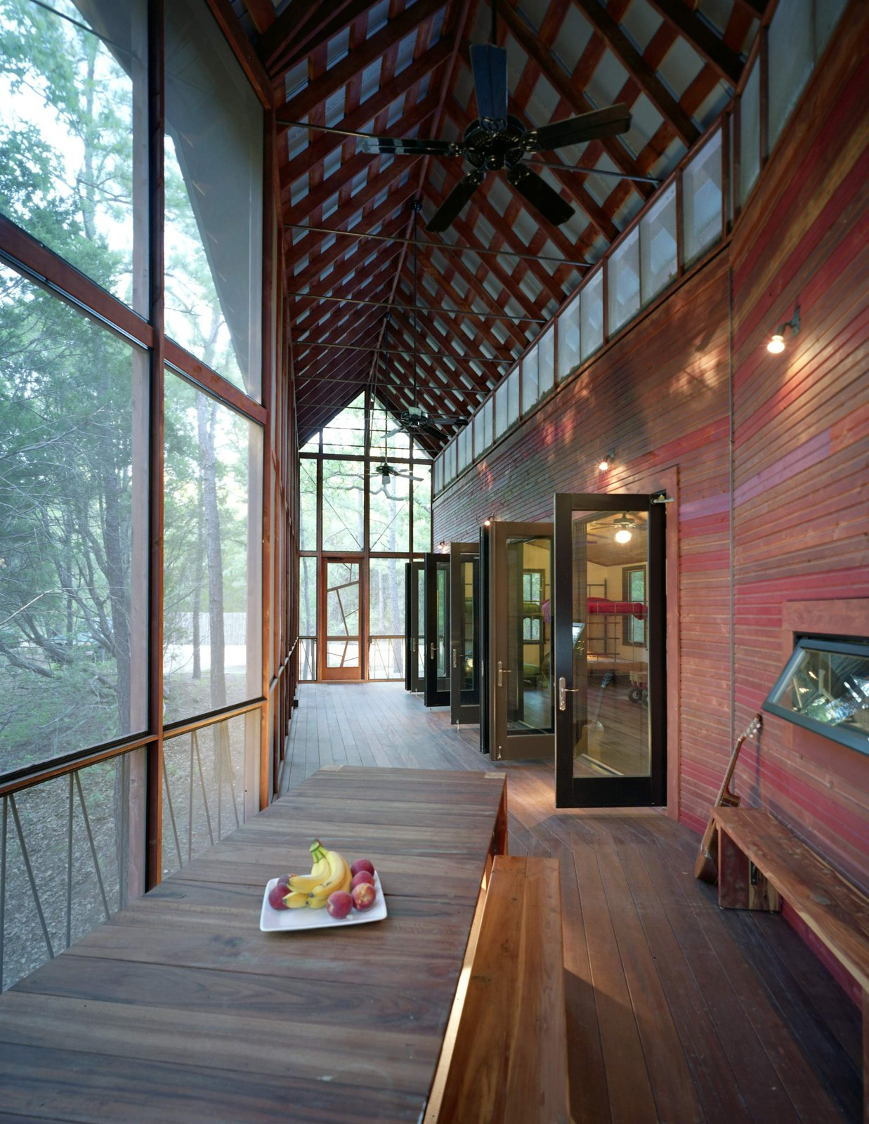 """A view back toward the entrance. The purlin ceiling beneath the porch's gabled Galvalum roof is made up of two-by-four cedar strips. A frieze of screened openings runs the length of the building, allowing a cross-breeze and extra light in, while ceiling fans keep the air circulating in summer. """"Animals, from deer to raccoons to all kinds of birds, come right up to the porch,"""" says Panton.  Texas Bunkhouse by Erika Heet"""