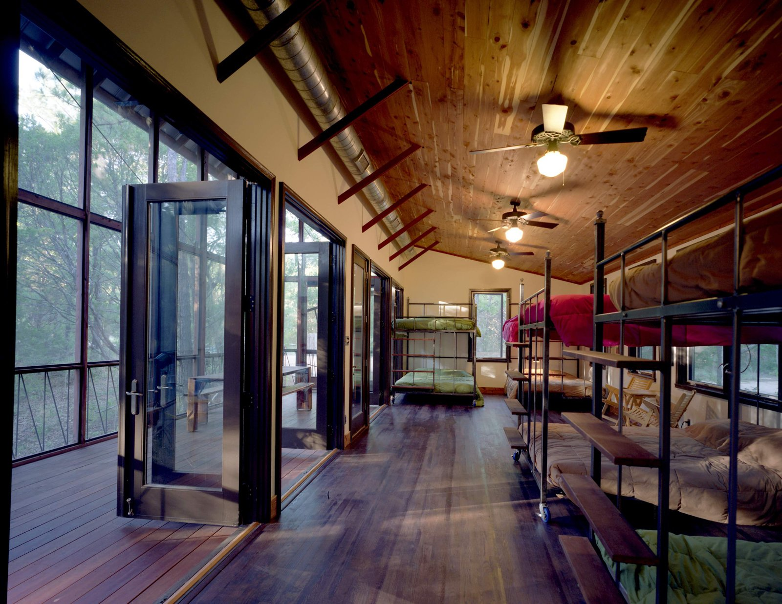 Panton placed several custom-made queen-size steel-and-wood bunk beds inside the bunkroom. All the beds are on wheels and fit through the double-side door openings, so they can be easily rolled into the porch for sleeping. Complementing the locally milled, insect-resistant cedar bunkroom ceiling are floors of purple-stained white oak (bunkroom) and the especially durable Brazilian Tigerwood (screen porch). Texas Bunkhouse by Erika Heet