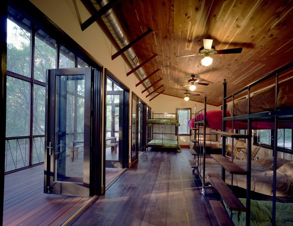 Panton placed several custom-made queen-size steel-and-wood bunk beds inside the bunkroom. All the beds are on wheels and fit through the double-side door openings, so they can be easily rolled into the porch for sleeping. Complementing the locally milled, insect-resistant cedar bunkroom ceiling are floors of purple-stained white oak (bunkroom) and the especially durable Brazilian Tigerwood (screen porch). Photo 11 of Texas Bunkhouse modern home