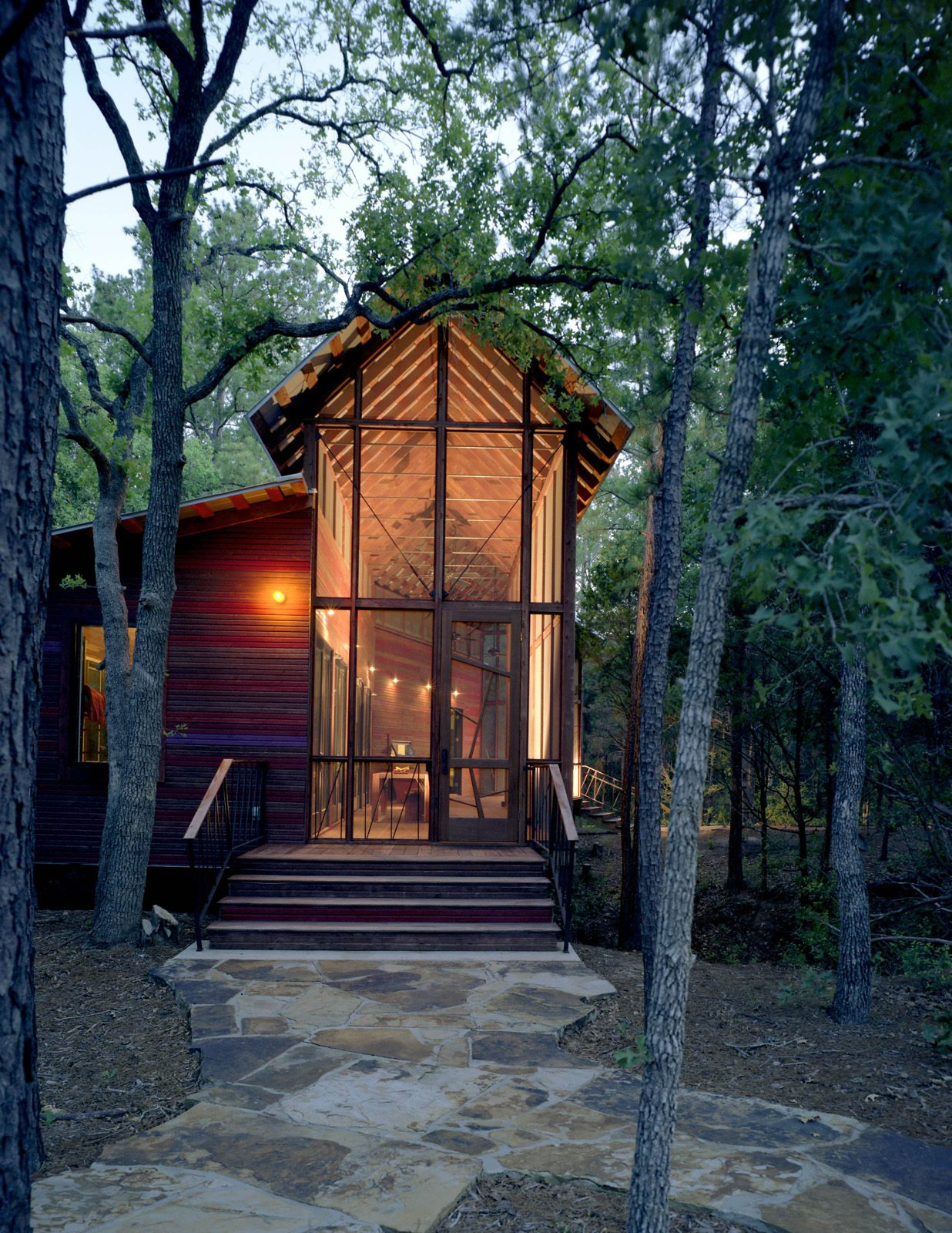 The architectural relationship between the bunkroom and porch, and the bunkhouse and the surrounding forest, is especially apparent at dusk, when the building reads as a kind of illuminated lantern.  Texas Bunkhouse by Erika Heet