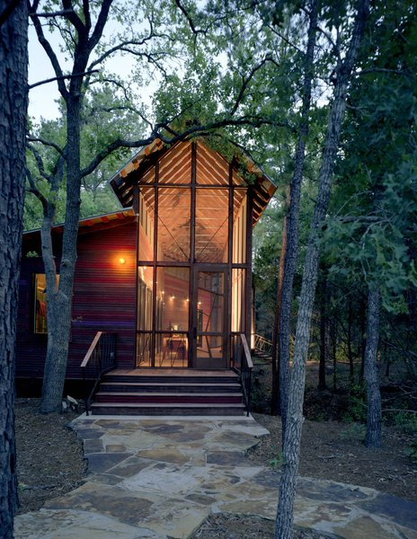 The architectural relationship between the bunkroom and porch, and the bunkhouse and the surrounding forest, is especially apparent at dusk, when the building reads as a kind of illuminated lantern. Photo 13 of Texas Bunkhouse modern home