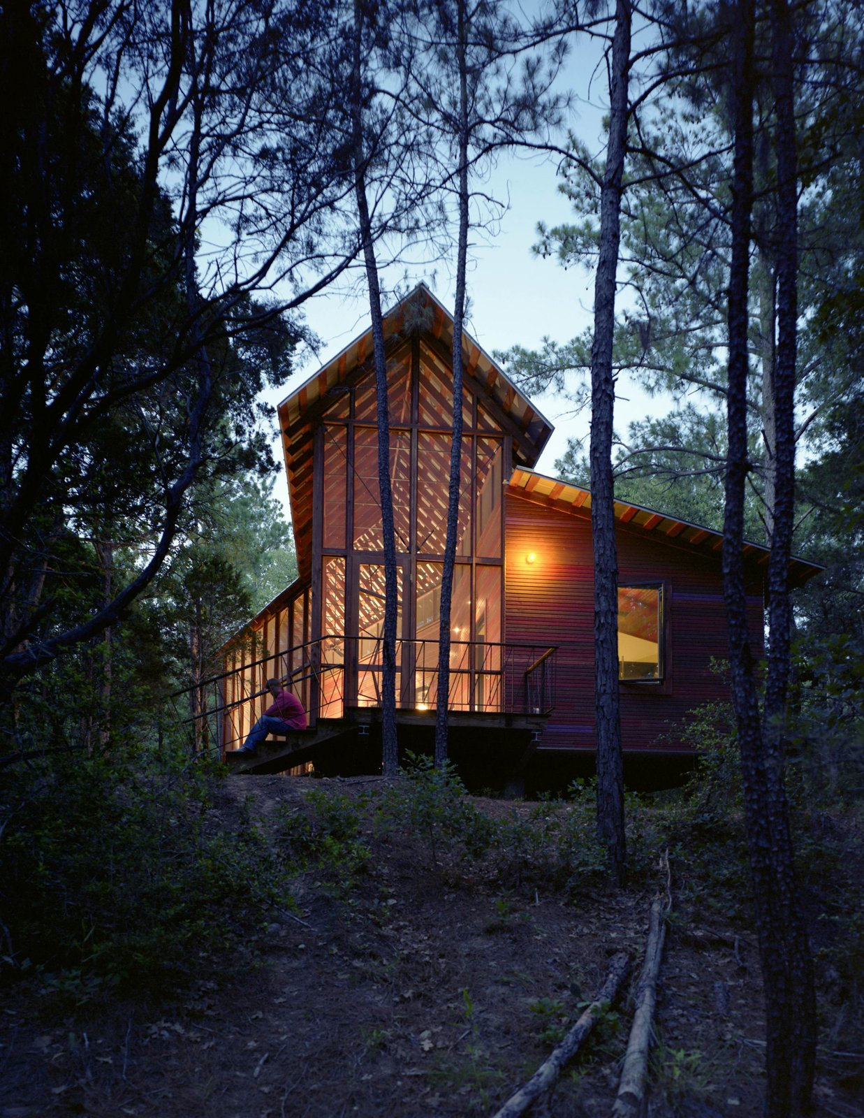 """I wanted more of a skeletal look for this house, and less of a chunky, log-cabin look,"" says Panton, who added stark steel bracing across the entire length of the porch's roof structure. Tagged: Exterior, House, Cabin Building Type, Wood Siding Material, Glass Siding Material, Shed RoofLine, and Gable RoofLine.  Photo 67 of 101 in 101 Best Modern Cabins from Texas Bunkhouse"