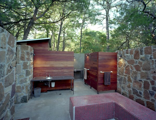 With its Brazilian Tigerwood enclosures, the outdoor bathhouse, which includes showers, sinks and dressing areas, references the nearby bunkhouse. Photo 17 of Texas Bunkhouse modern home