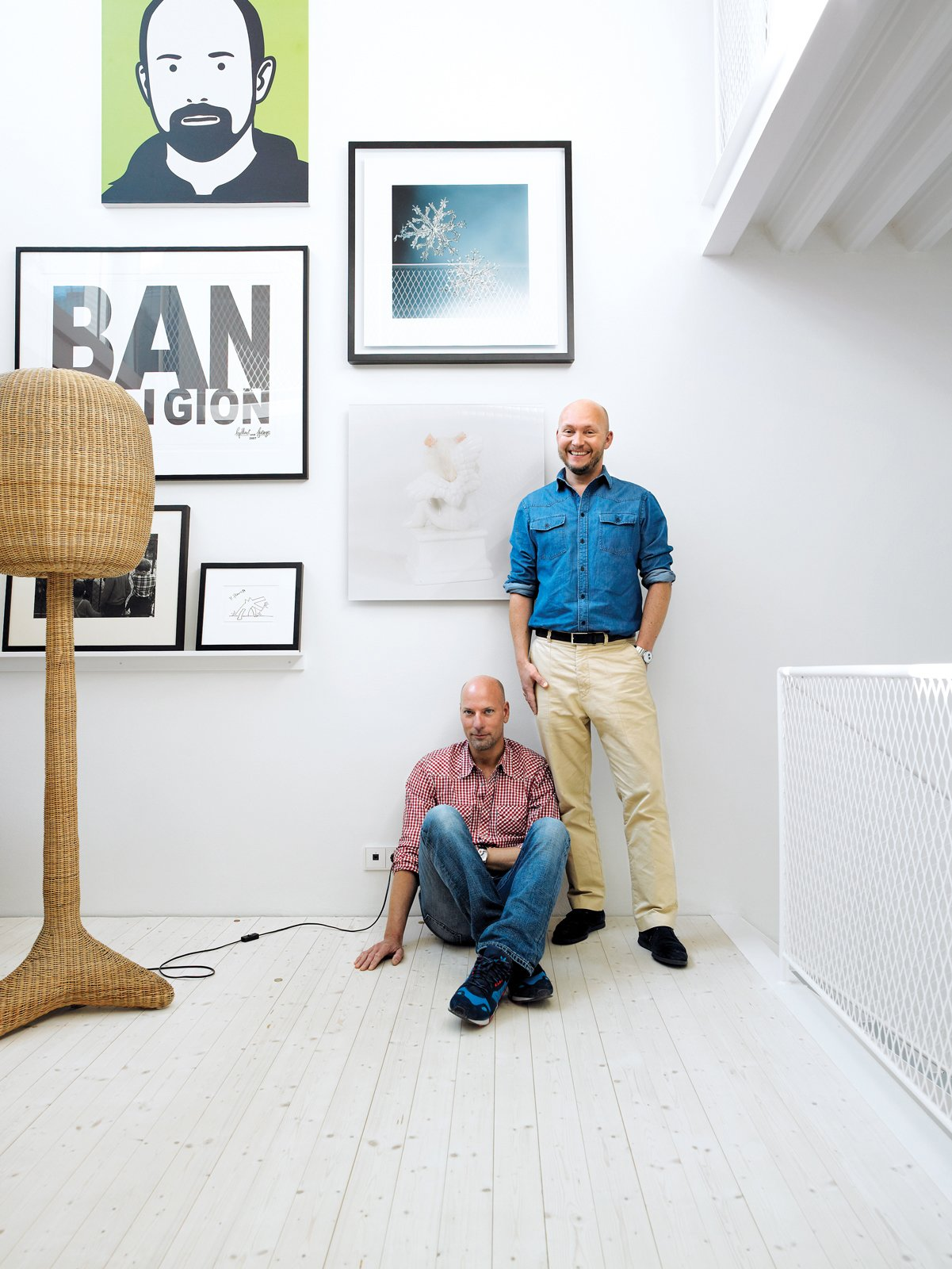 Johnny Lökaas and Conny Ahlgren pose in their living room with some of their art collection, which includes a Julian Opie portrait and works by Keith Haring and others. Space to show the art and good light for viewing it were the priorities.
