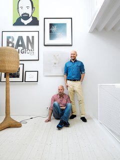 Contemporary Nordic Town House - Photo 3 of 14 - Johnny Lökaas and Conny Ahlgren pose in their living room with some of their art collection, which includes a Julian Opie portrait and works by Keith Haring and others. Space to show the art and good light for viewing it were the priorities.
