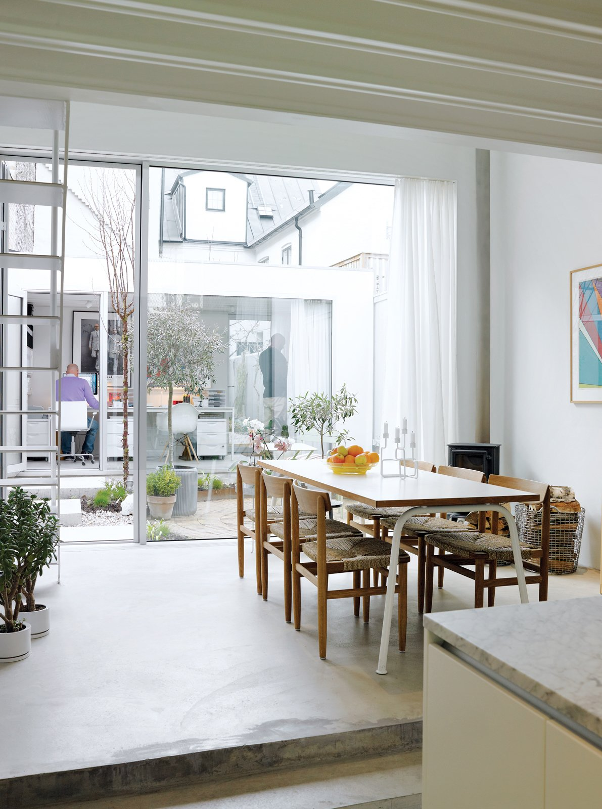 The view from the kitchen is as lively as it is light, taking in the dining area, tiny courtyard garden, and the separate office building backed by the jumble of old buildings to the rear. The rustic dining chairs are by Börge Mogensen from Karl Andersson & Söner. Contemporary Nordic Town House - Photo 7 of 14