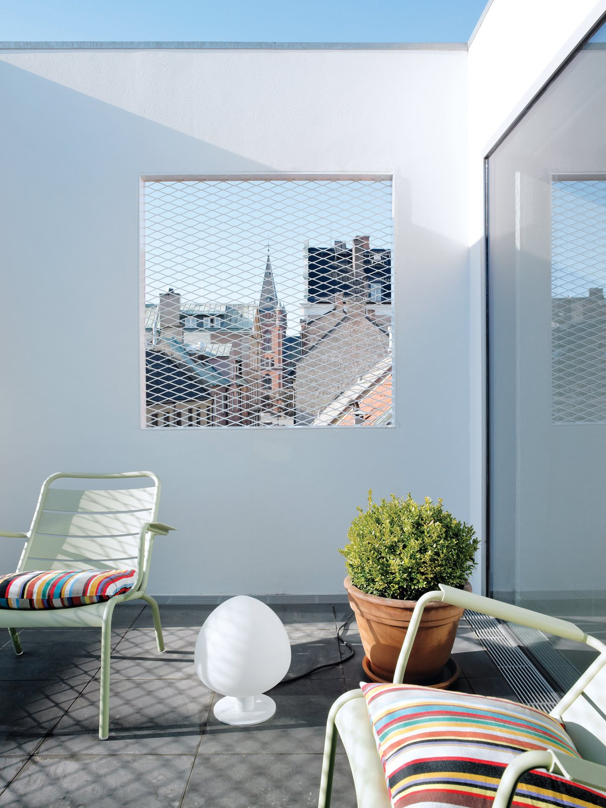 "The roof terrace offers a view of the town square, ""filtered"" through a grille. Tagged: Outdoor and Rooftop.  Photo 13 of 14 in Contemporary Nordic Town House"