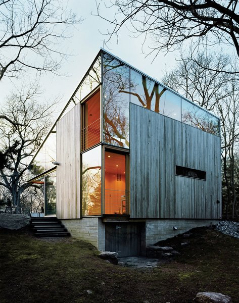 "Sheets of unframed glass fill the spaces between the building's operable windows and the sloping eave of the roof, giving the house, as architect Alan Organschi puts it, ""the feel of coming apart at the seams—of surfaces unhinged."""