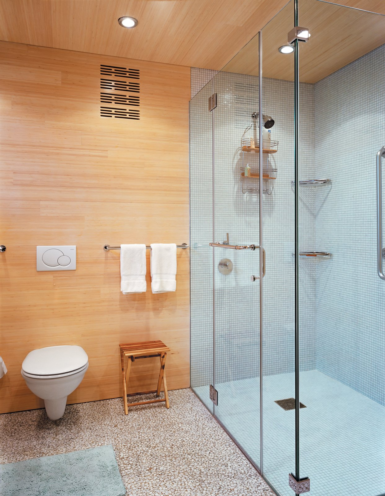 The floors, walls, and ceilings are coated in FSC-Certified laminated bleached bamboo. Tagged: Bath Room, Terrazzo Floor, One Piece Toilet, Recessed Lighting, Enclosed Shower, and Ceramic Tile Wall.  Photo 7 of 10 in Striking Angular Cottage in Connecticut
