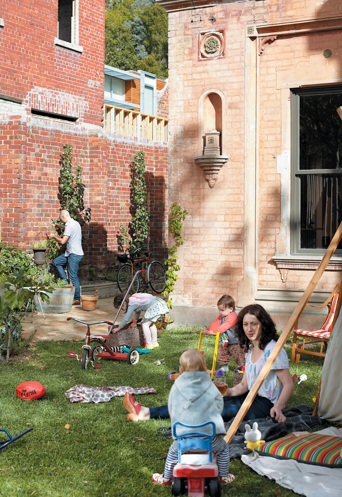 From the buzzing front yard the Gorman-Angelucci family (and a young friend) is always at it. Dean Angelucci tends the garden and Lisa Gorman minds the kids—Pepa (with basket) and Hazel (in red)—who are hard at play. Tagged: Outdoor and Grass.  Photo 5 of 9 in 1860s Stable Modernized in Melbourne