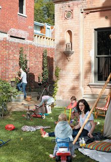 1860s Stable Modernized in Melbourne - Photo 5 of 9 - From the buzzing front yard the Gorman-Angelucci family (and a young friend) is always at it. Dean Angelucci tends the garden and Lisa Gorman minds the kids—Pepa (with basket) and Hazel (in red)—who are hard at play.