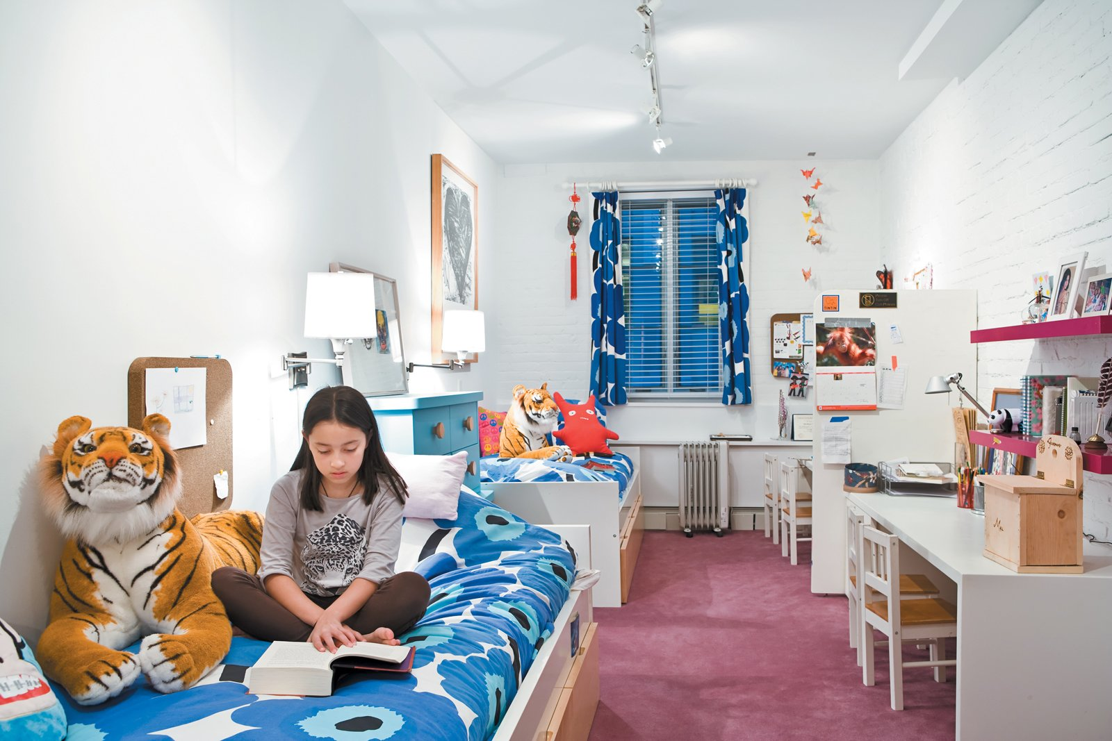 The girls' narrow bedroom gets natural light from a single window. White paint and furniture (accented with Marimekko print linens) keep the space feeling bright. Tagged: Carpet Floor, Bed, Kids Room, Night Stands, Dresser, Shelves, and Storage.  Photo 2 of 12 in Fine Dine-ing
