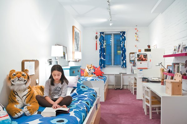 The girls' narrow bedroom gets natural light from a single window. White paint and furniture (accented with Marimekko print linens) keep the space feeling bright.