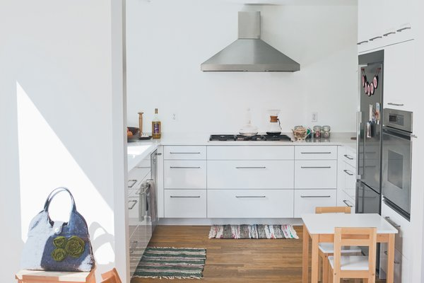 The kitchen maintains the white hue of the house, and the couple finished its custom cabinetry in a glossy thermofoil to emphasize its utility as part of the central core.