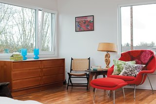 In the master bedroom, a red Womb chair and ottoman by Eero Saarinen are offset by furniture from Waechter's grandparents.