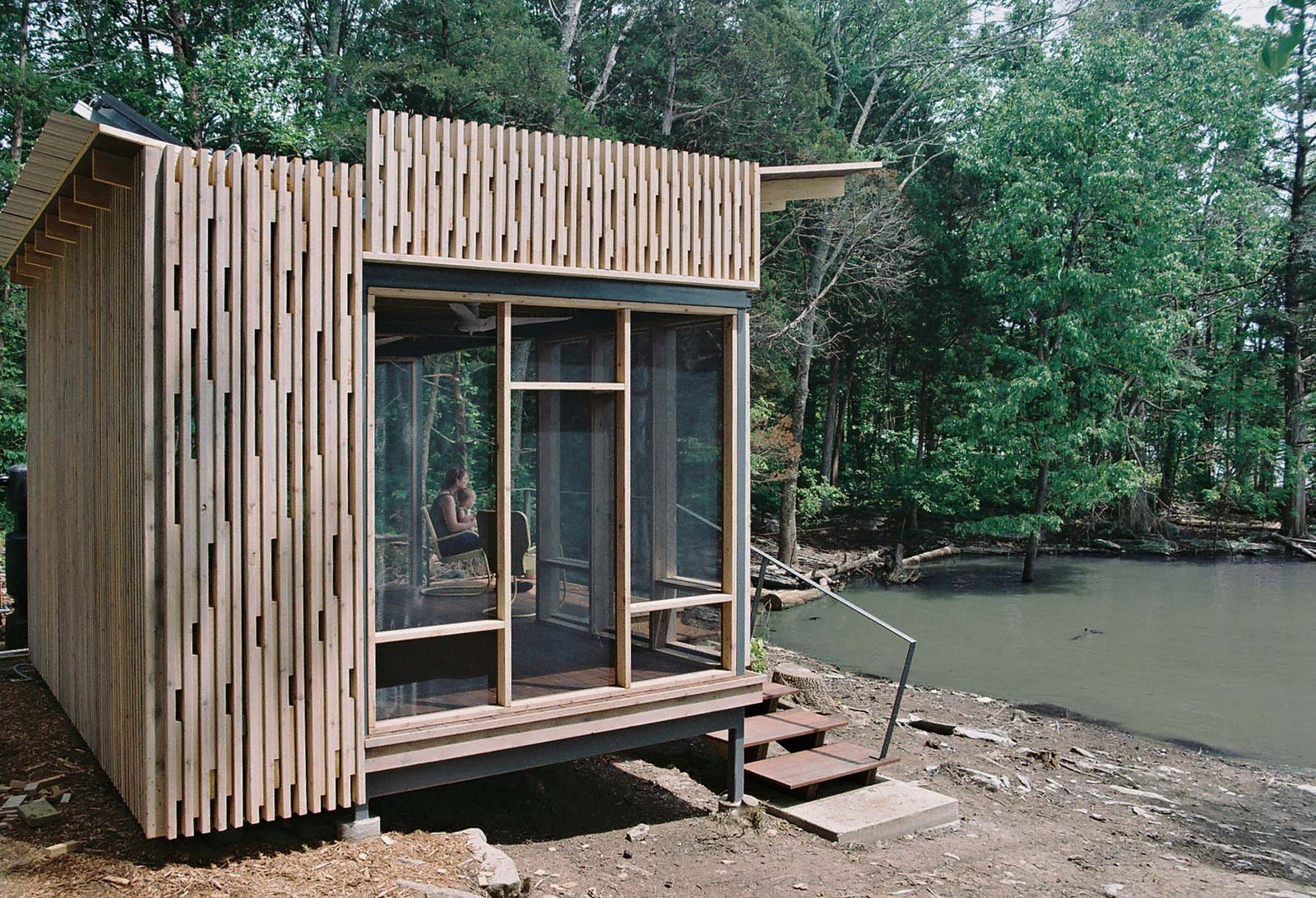 "For the Knoxville-based CEO of environmentally-focused marketing firm the Shelton Group, building an off-the-grid lakefront pavilion in Sharps Chapel, Tennessee, wasn't so simple. With the help of architect Brandon Pace, she built a small prefabricated cabin on a ""funky piece of property"" on Norris Lake, a man-made reservoir. Tagged: Exterior, Cabin Building Type, and Wood Siding Material.  Photo 4 of 4 in How to Build an Off the Grid Cabin"