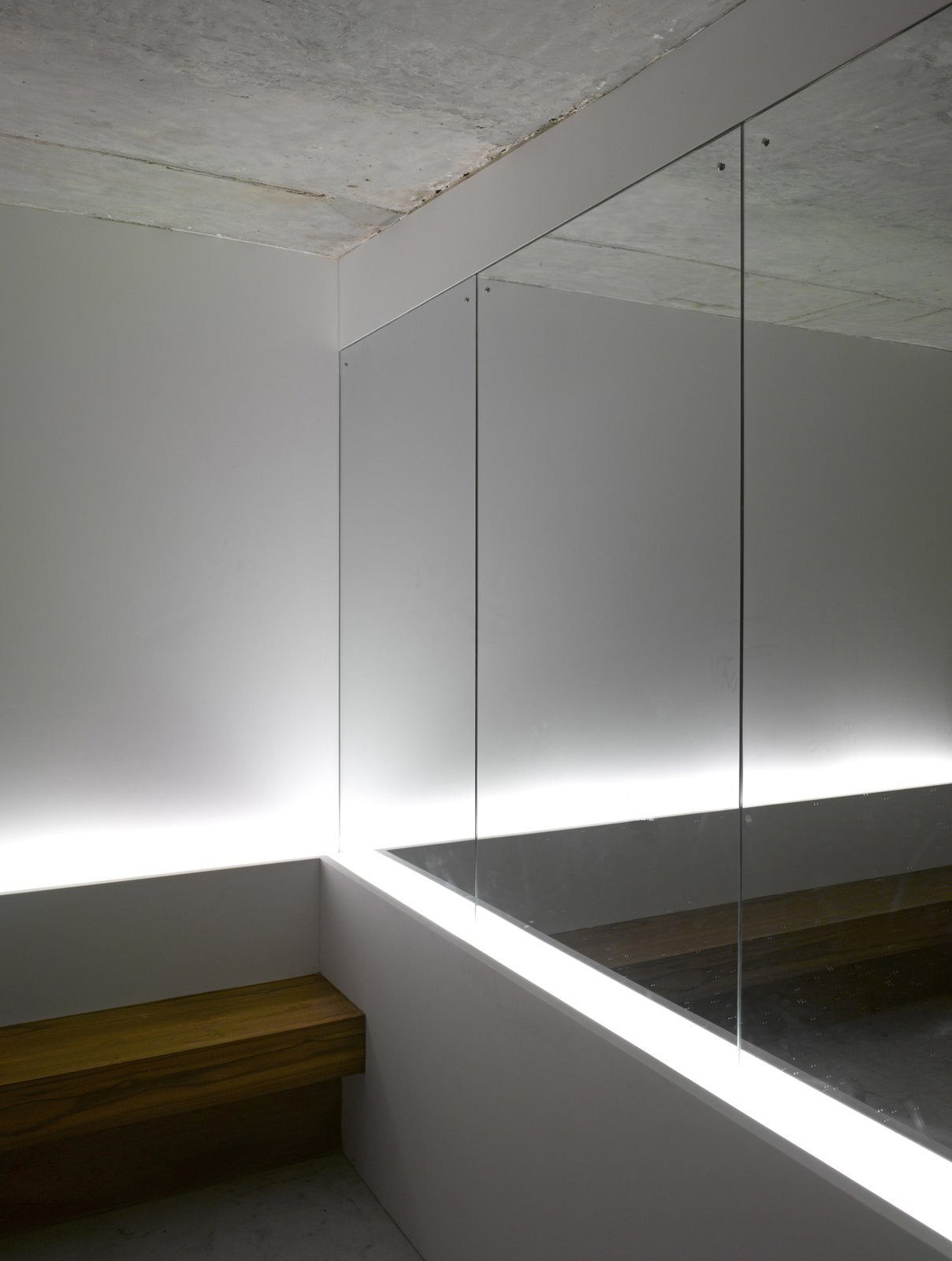 "A mirror near the mailboxes in the lobby gives the illusion of more space. A team from Lighting Planners Associates, based in Japan, added the uplights behind the bench for effect. The architectural firm left the ceilings raw concrete to make the space ""more enigmatic,"" says Schultz."