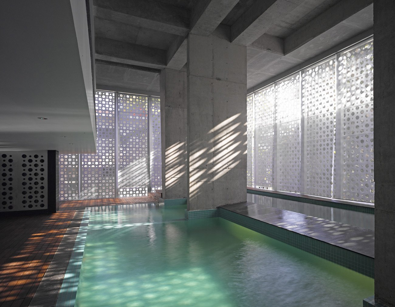 The aluminum casing creates a play of light and shadows as the sun moves across the building. A lap pool, at right, spills over into the main pool.  Photo 12 of 17 in A Modern Aesthetic in Mumbai