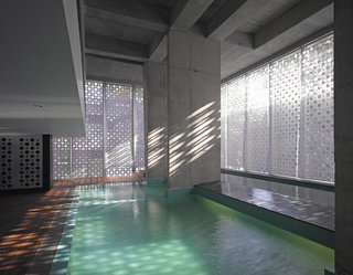 The aluminum casing creates a play of light and shadows as the sun moves across the building. A lap pool, at right, spills over into the main pool.