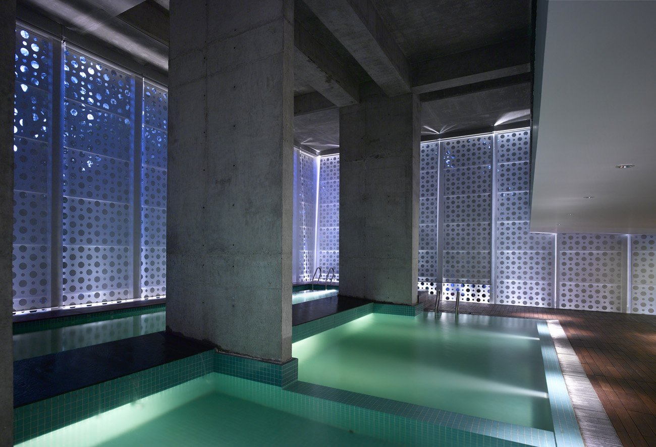 "An interplay of geometries in what Khanna calls ""the belly of the building."" Uplights create new angles of light, raw concrete retains a rough edge and square pool tiles add texture and color while offsetting the perforated circles. The dropped ceiling at right is part of a small balcony overlooking the pools; beneath it is a sitting area.  Photo 13 of 17 in A Modern Aesthetic in Mumbai"