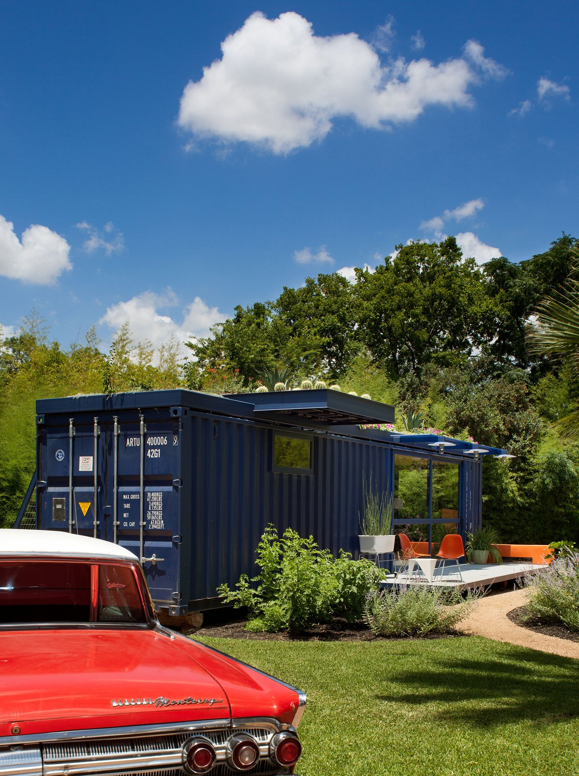 Hill's 1962 orange Mercury Monterey complements the blue of the container, whose original opening was retained on one end as the entrance to the garden storage shed. Tagged: Exterior, Shipping Container Building Type, and House.  Photo 5 of 17 in Smaller in Texas