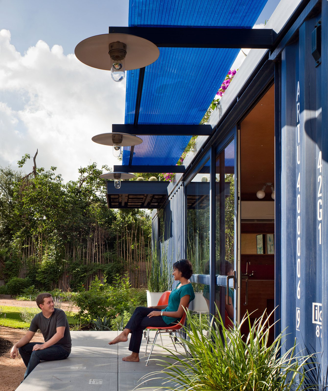 Friends of both the resident and the architect post up on the porch. Poteet attached beams to the container and topped them with a Polygal sheet for shade. The lamps were custom made by the architect from recycled tractor parts fitted with vapor lamps.  Shipping Containers by Dwell from Smaller in Texas