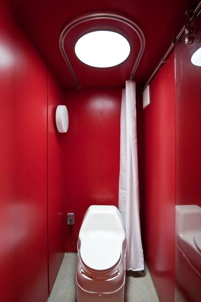 Maximizing space was of utmost importance in the 8-by-4-foot bathroom, which consists of an open shower in front of an electric composting toilet by Sun-Mar. Poteet and Hill chose a red sheet metal for the walls and laid down a non-slip epoxy flooring.