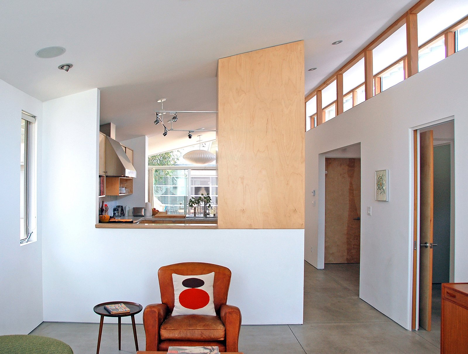 Oreck incorporated a pitched ceiling to allow light in from all sides, and added, beyond the series of structural beams, clerestory windows he describes as âsort of a light spine that runs through most of the house.â To maximize the feeling of spaciousness, the living room is partially open to the kitchen and dining room, beyond. At right is the door to the third bedroom/office and the rectangular opening leads to a bedroom and bathroom. The radiant-heat floors are powered by the sun: âIt just seemed silly to build a new house in the 21st century in Los Angeles and not utilize solar power,â says Orlovski.  Shining Examples of Clerestory Windows by Luke Hopping from Double Time: Bungalow Redux