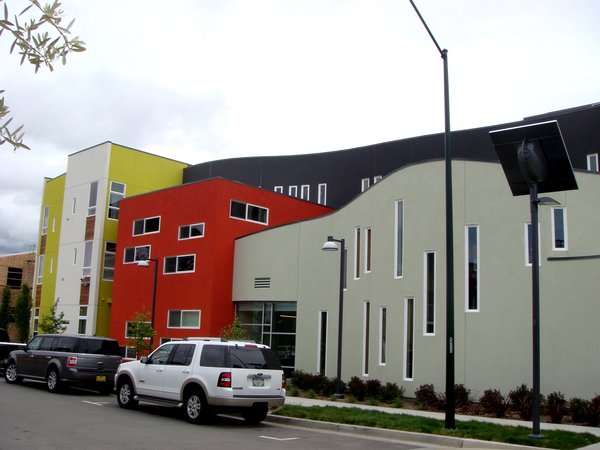 Bright colors, contemporary detailing, and plays on mass and void are seen throughout the development. The high-density apartment building on the southeastern corner of the site reflects some of the unique architectural features of the project. The US Green Building Council awarded the apartment building a LEED for Homes Platinum rating.