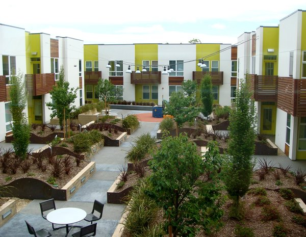The large rooftop courtyard is filled with lush greenery, a jungle gym, picnic tables and benches.