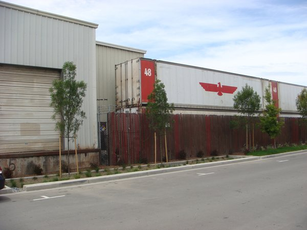 The development is bordered by industrial zones with merely a street as a buffer. Shipping containers to the south of the site serve as a reminder of Tassafaronga's context. Bridget Galka, who is the senior development director for the Oakland Housing Authority, says that the position of the development on the cusp of residential/industrial zones allowed for more potential to develop the area.