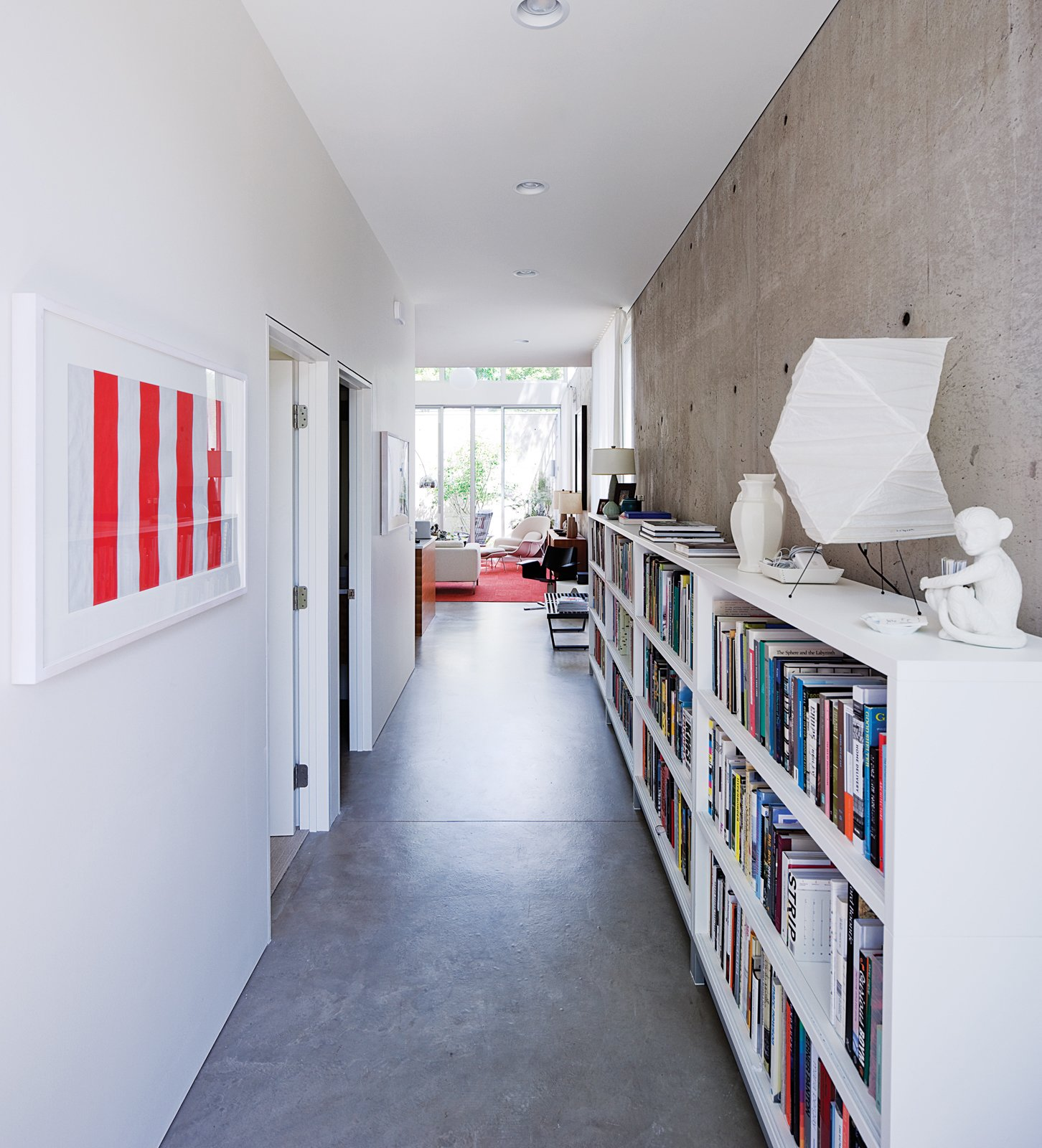 A portion of Blauvelt's 3,000-book library is archived in the long entry hall where the geometry of a Noguchi lamp plays off a pair of minimalist prints by Daniel Buren. Tagged: Hallway and Concrete Floor.  Photo 1 of 29 in Modern Urban Retreat in South Minneapolis