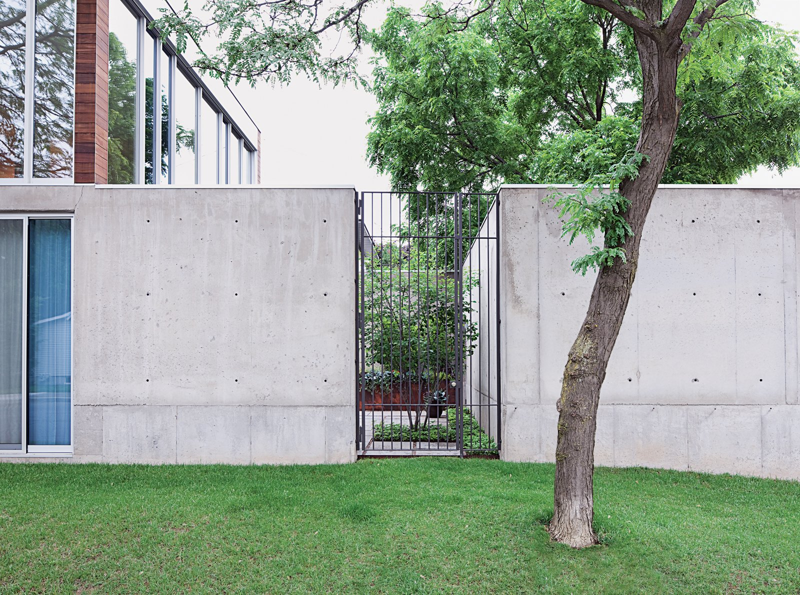 A tall steel gate grants entry to the courtyard.  Photo 14 of 29 in Modern Urban Retreat in South Minneapolis