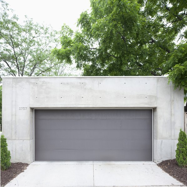 The darker gray garage door offers a chromatic and textural contrast to the concrete shell.