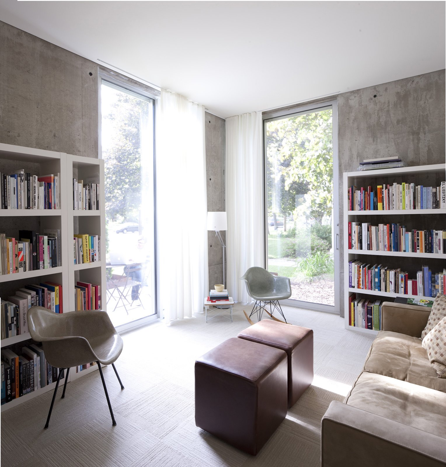 The study houses not only a pair of plastic Eames shell chairs but much of the couple's large collection of architecture and design books.  Photo 25 of 29 in Modern Urban Retreat in South Minneapolis