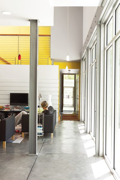 Susan relaxes on an Ikea sofa. The yellow accent wall and high ceilings enhance the lightness of the room.