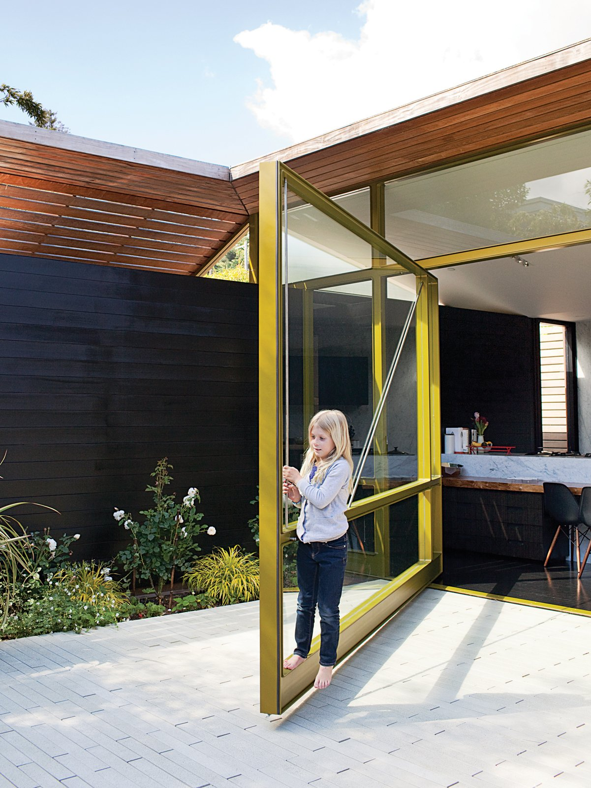 Thanks to clever engineering by Sand Studios, seven-year-old Macy can operate the 2,000-pound door. Tagged: Doors, Exterior, Swing Door Type, and Metal.  20 Homes with Inspiring use of Glass by Diana Budds from Designed In-House