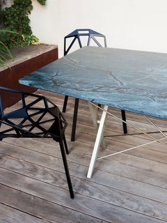 Can't find the right table for your space? Another option is to have a custom top cut for a recycled base, which is what the Deams did for their outdoor dining area. They had an existing Scissor table base by Bay Area designer John Randolph sitting unused, so Chris had a piece of hardy soapstone (it stands up to high temperatures) cut to match by Fox Marble. A subtle facet at each corner plays off the base's design and lends a more intimate feel to the long table. For a fraction of the cost of a full piece, the bases of design classics are often available on Craigslist and eBay.