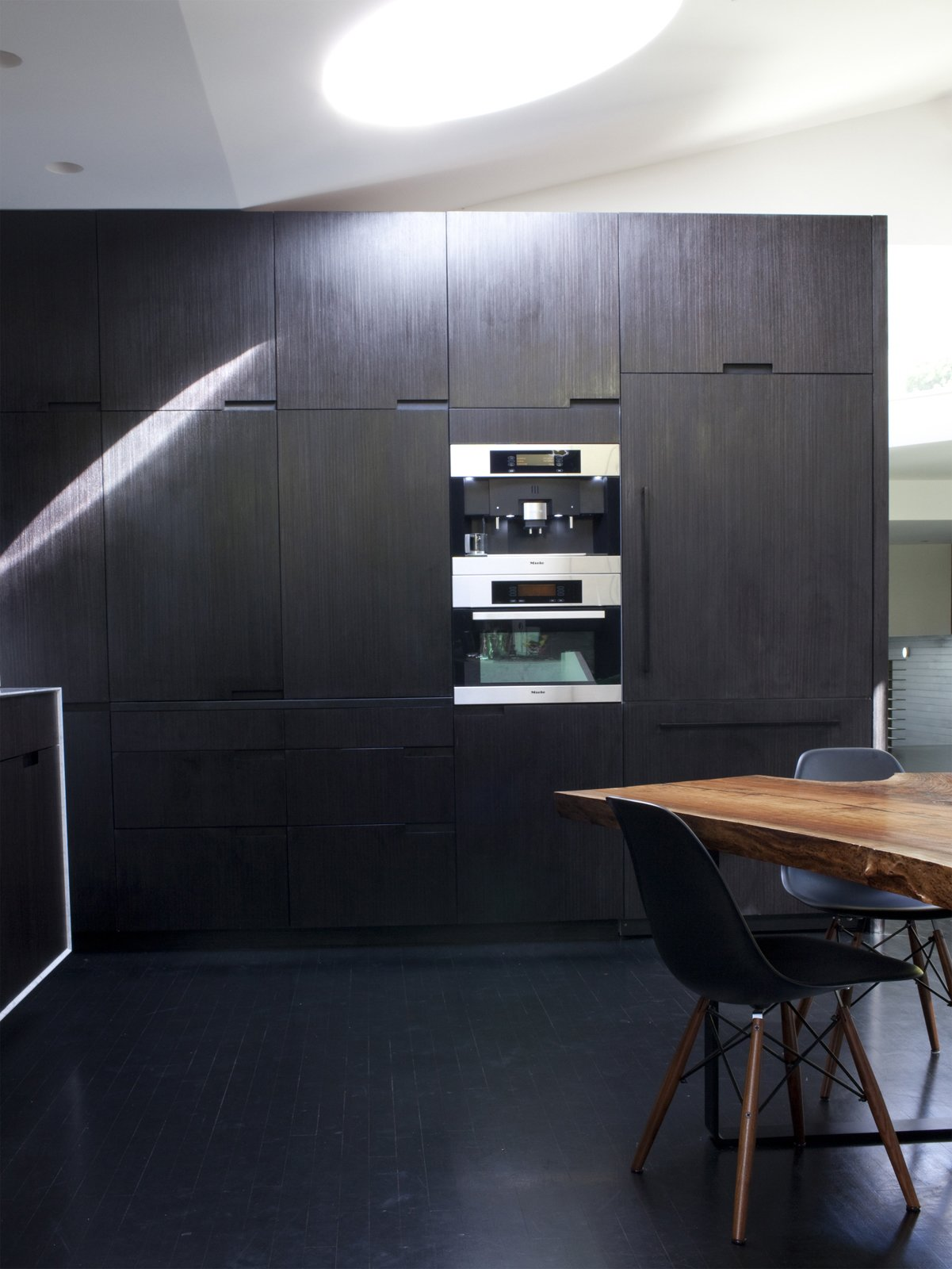 A wall of built-ins in the kitchen houses a raft of Miele appliances including a refrigerator, microwave, and espresso machine. Tagged: Kitchen, Wall Oven, and Dark Hardwood Floor.  Photo 10 of 11 in 10 Stunning Ways to Use Black in Your Kitchen from Designed In-House