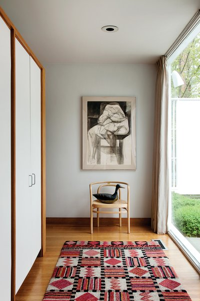 The main entry, located off the front courtyard is more practical than grand. The door opens onto a PK15 chair by Poul Kjaerholm and built-in coat cabinets that direct movement to either side of the hall and into the living area.