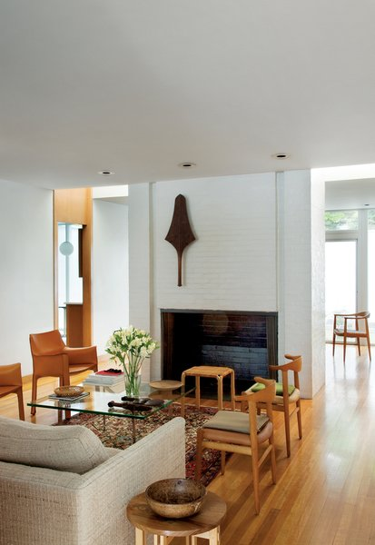 A club from the Fiji islands is mounted on the wall of the fireplace that divides the living and dining rooms. The dining room—furnished with two Cab chairs by Mario Bellini for Cassina, a pair of Cowhorn chairs by Hans J. Wegner for Johannes Hansen, the Barcelona Table by Mies van der Rohe for Knoll, and a Y61 stool by Alvar Aalto for Artek—has no windows, but lightwells on either side of the chimney provide brightness. Another design by Wegner, the Chair, peeks out from the dining room.