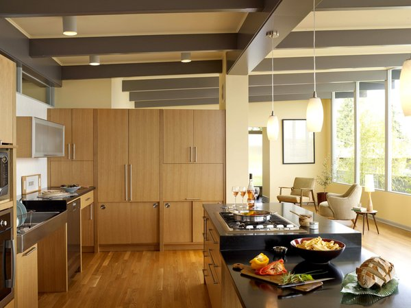 """The kitchen cabinet wall provides storage and workspace, yet retains an open feel by stopping well beneath the ceiling. Sliding cabinets at the bottom reduce the number of space-hogging swinging cabinet doors, and a KitchenAid mixer is hidden behind the horizontal lift-up cabinet at right, which recesses into the wall. """"The cooktop is at a height where I can see into my pot of spaghetti sauce,"""" says Braitmayer. """"I cook in this kitchen more than ever before."""" The countertops are heat-resistant, allowing more options for the person cooking. To the right of the sink is an ADA-compliant dishwasher from Miele. The pendant lights are from Progress Lighting."""