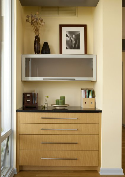 """Just inside the patio doors and near the dining table is Braitmayer's work nook. The top drawer flips out to become a desk; the top cabinet slides straight up to reveal more storage. """"It's very organized,"""" says Sundstrom."""