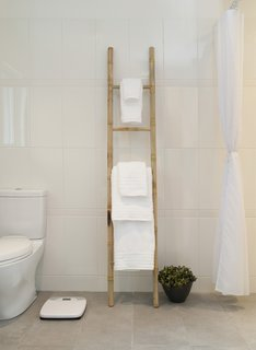 Highly Accessible - Photo 10 of 16 - A simple bamboo ladder holds towels in the master bathroom, whose floors are radiant-heated. Just beyond the curtain at right is the curbless shower. Toto toilet.