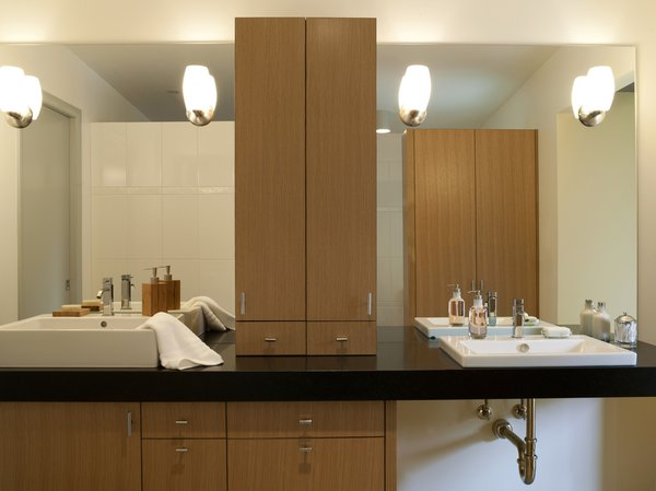 The master bathroom has complementary his-and-hers sinks from Duravit, and Cifial faucets. Reflected in her mirror is a cabinet with a larger, full-length mirror inside.