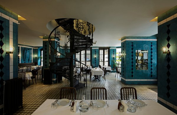 Old meets new with an iron staircase, tiled floors and walls, and chairs Anjelique restaurant.