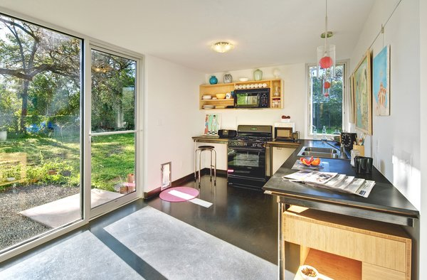 "When planning the house as a single man, Wong asked for a ""bachelor's kitchen,"" noting that he could only make frozen pizza and sandwiches. The simple setup, which faces East and receives the bright morning sun, still accommodates the family well. The little door is shared by Wong's two Italian greyhounds, Sage and Solo, and the family cat, Coco. As throughout the house, the Low-e doors and windows are from Anchor Ventana. Richlite countertops."