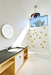 "Light floods the second-floor bath, which is housed within a birch-ply ""box"" also containing storage. The water is heated by a tankless, on-demand unit from Rinnai. The architects continued the tile motif for the bath downstairs; the honey-colored tiles are from Dal-Tile. The lamp is by Kathleen Ash of Studio K Glass."
