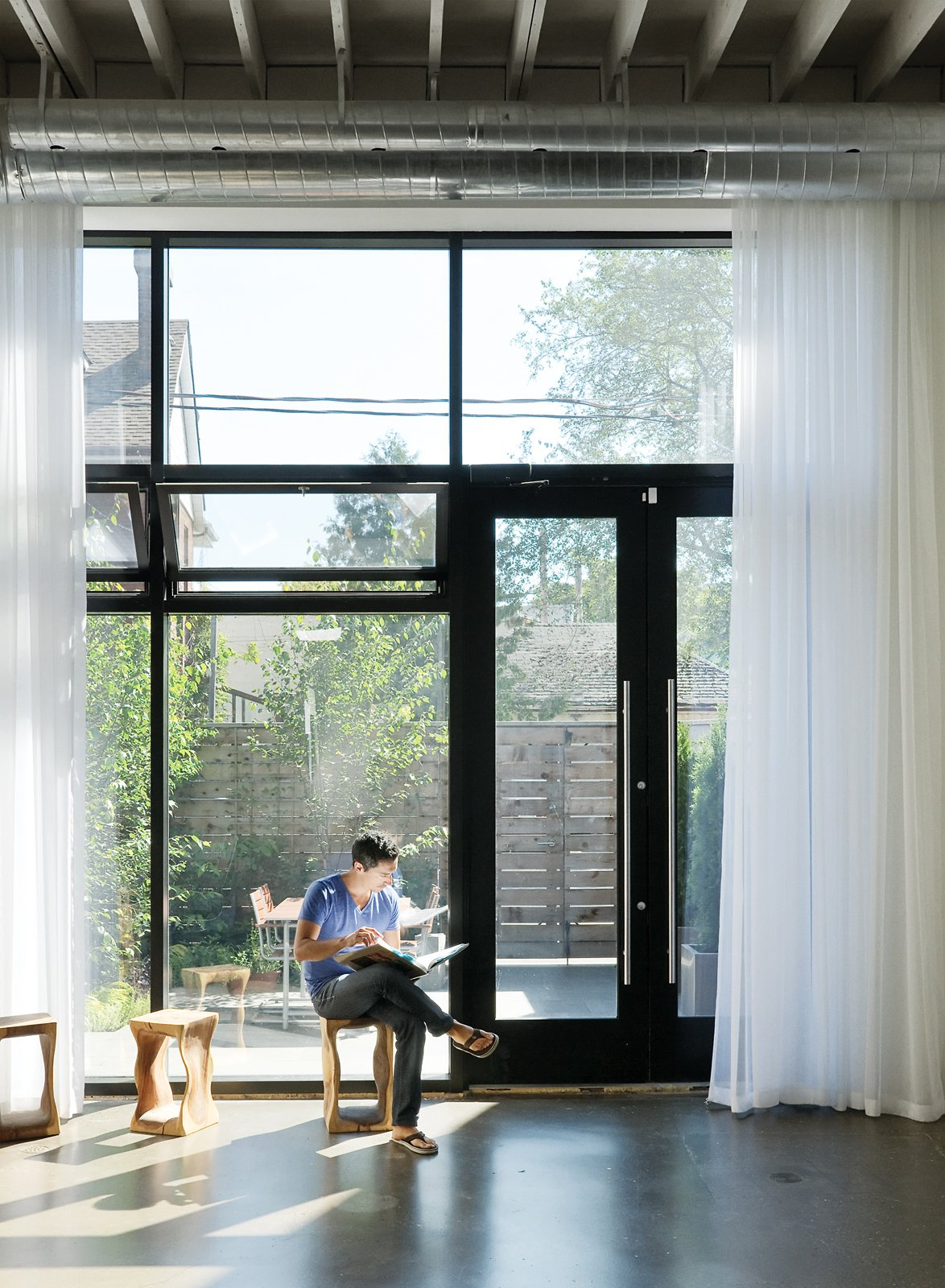 In the house's front room Monkman relaxes on a stool from local retailer Andrew Richard Designs. A new window system draws in sunlight and views of the front courtyard designed by local landscape architect Terry McGlade, the building's former owner.